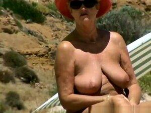 Vovó Busty Nudista, Vovó Busty Nua Em Praia Nudista Com Chapéu Em Sua Cabeça E óculos De Sol Desfrutando Do Dia Ensolarado E Colocando Creme De Proteção Solar Sobre Seu Corpo. Porn